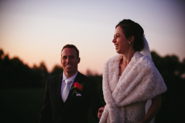 Newlywed couple smiling at sunset