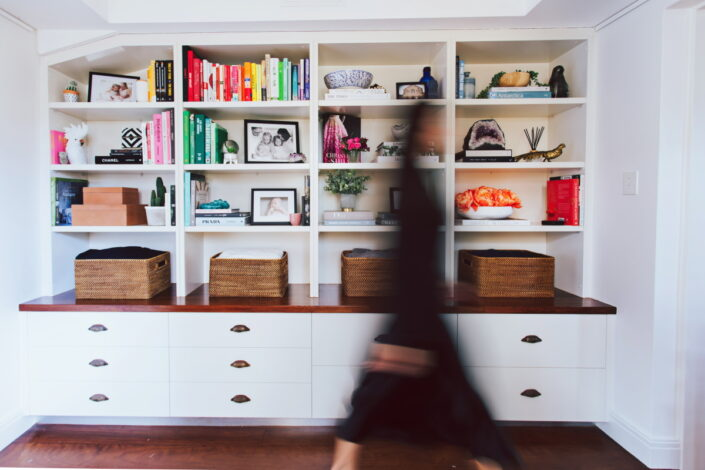 Woman walks past bookshelf