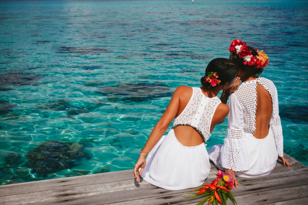 Two brides pose on a beautiful lagoon