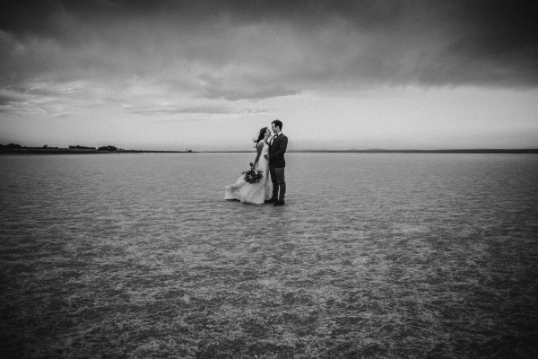 Wedding couple pose on salt lake