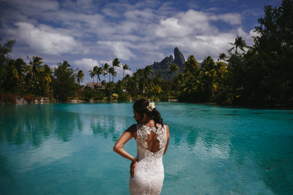 Model poses in wedding dress beside a Bora Bora lagoon