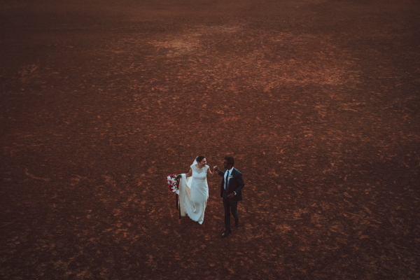 Newlywed couple walking across red earth quadrangle